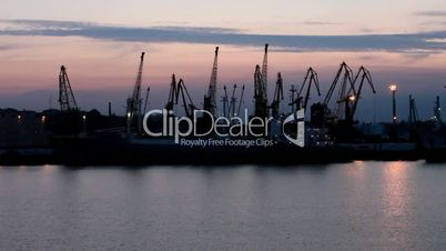 Silhouette of several cranes in a harbor, shot during sunset. Odessa, Ukraine (Time Lapse)