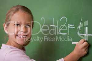 Happy schoolgirl writing a number