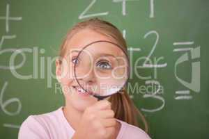 Playful schoolgirl looking through a magnifying glass