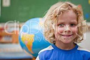 Schoolboy posing in front of a globe