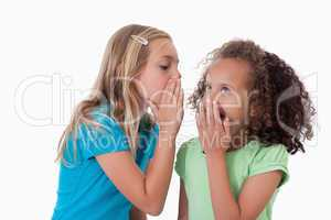 Young girl whispering a secret to her friend