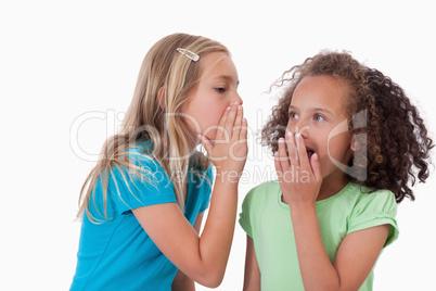Cute girl whispering a secret to her friend