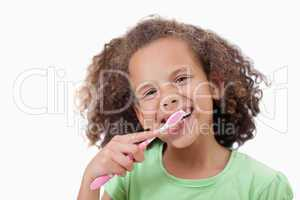 Smiling girl brushing her teeth
