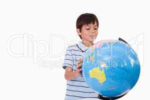 Smiling boy looking at a globe