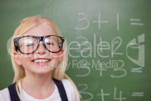 Smart schoolgirl posing in front of a blackboard