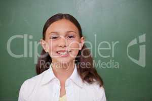 Cute schoolgirl standing in front of a blackboard