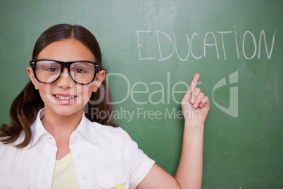 Smart schoolgirl pointing at a word