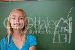 Blonde schoolgirl posing in front of a blackboard
