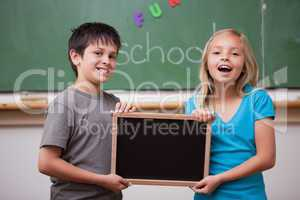 Happy pupils holding a school slate