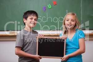 Smiling pupils holding a school slate