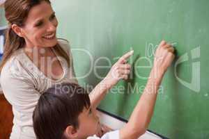 Schoolteacher helping a schoolboy doing an addition