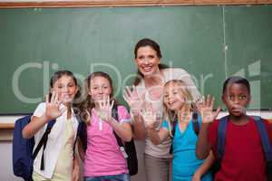 Schoolteacher and her pupils waving at the camera