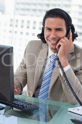 Portrait of a businessman working with a monitor while being on