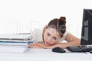 Tired secretary leaning on her desk
