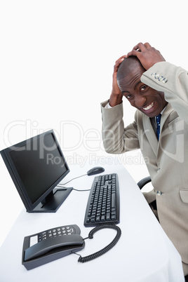Side view of a furious businessman using a monitor