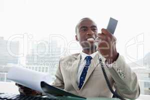 Angry businessman looking at his phone handset