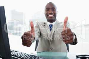 Entrepreneur working with a computer with the thumbs up