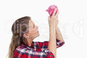 Woman looking inside a piggy bank