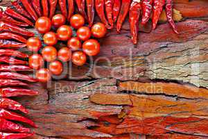 ripe cherry tomatoes and dried red chillies on rustic stripped bark