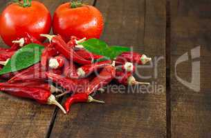 Dried red chillies and tomato on a rustic wooden table