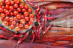 Basket of ripe cherry tomatoes and dried red chillies on rustic