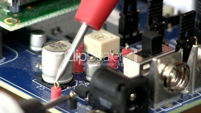Technician probes circuit board; 4