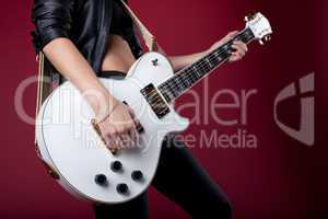 rock woman in black leather posing with guitar