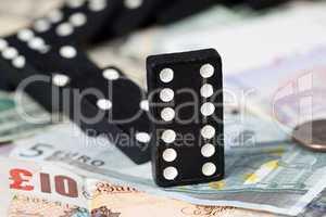 Fallen dominoes on bank notes
