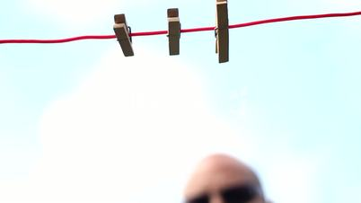 Male - Hanging money with pegs on a clothesline