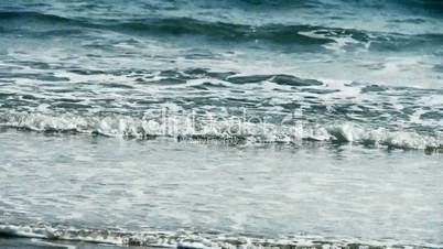 nice waves on sandy beach,white surge.