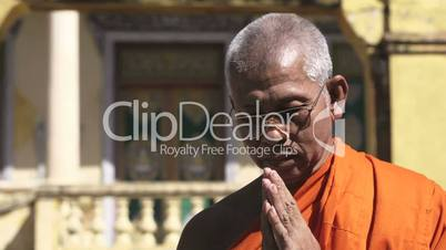 Portrait of senior buddhist monk with eyeglasses saluting and bowing with joined hands in temple, Phnom Penh, Cambodia, Asia