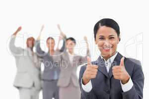 Saleswoman with cheering team behind her giving approval