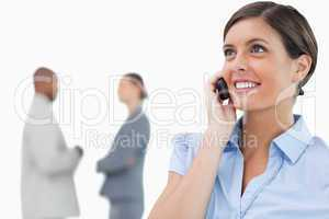 Smiling businesswoman with mobile phone and associates behind he