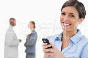 Smiling saleswoman with mobile phone and associates behind her