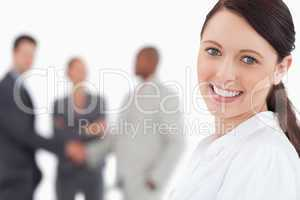 Smiling businesswoman with three associates behind her