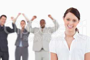 Smiling saleswoman with cheering associates behind her