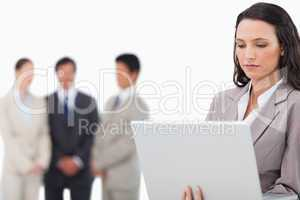Saleswoman with laptop and colleagues behind her