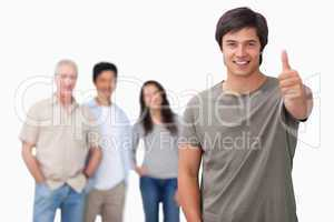 Smiling man with friends behind him giving thumb up