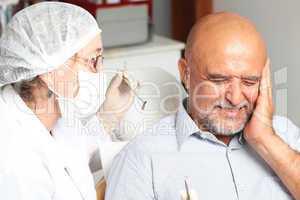 Mann mit Zahnschmerzen beim Zahnarzt