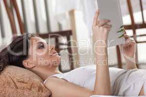 young woman lay in bed and read book