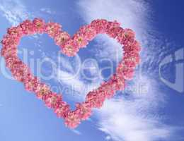 Heart from pink roses against the blue sky