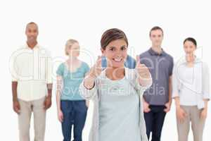 Close-up of a woman smiling giving the thumbs-up with people beh