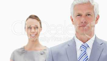 Close-up of a serious white hair businessman with a woman smilin