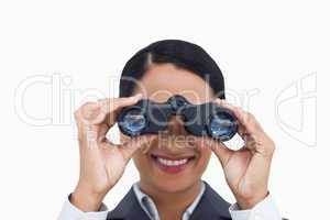 Close up of smiling saleswoman using spy glasses