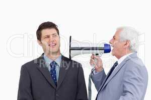 Close up of mature businessman with megaphone yelling at employe