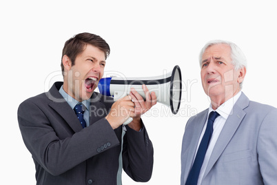Close up of businessman with megaphone yelling at his boss