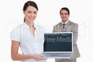 Smiling saleswoman presenting laptop screen with colleague behin