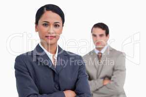 Saleswoman with arms crossed and colleague behind her