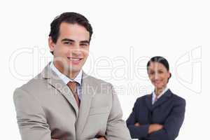 Smiling salesman with co-worker behind him