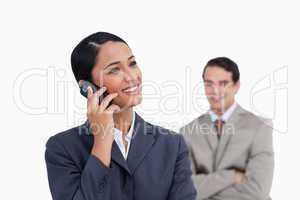 Smiling saleswoman on her mobile phone and co-worker behind her